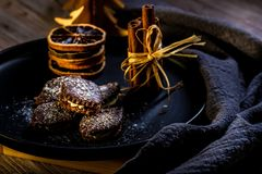 Brown chocolate sweets stuffed by cream on black plate with cinnamon stock images