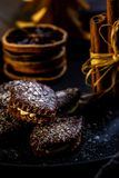 Brown chocolate sweets stuffed by cream on black plate with cinnamon royalty free stock photography