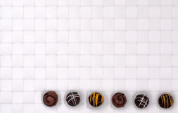Brown chocolates on a white background Stock Photos