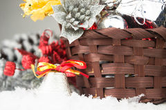 Brown Christmas basket with silver and gold toys on a white wooden background Royalty Free Stock Photos