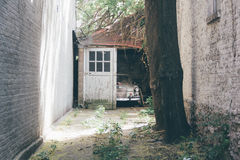 Brown Classic Car Parked Next to a Gray Wooden Door and Brown Tree Trunk Stock Images