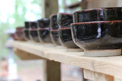 Brown clay bowls. On a plain wooden shelf Stock Photography