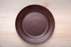 Brown clay dish standing on table. Brown clay dish standing on a wooden table Royalty Free Stock Image