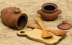 brown clay pitcher,clay pot ,cutting Board and spoon with a fork Stock Photos