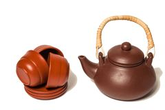 Brown clay teapot with wooden handle and three cups and round di royalty free stock images