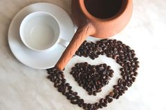 brown clay Turk for cooking Turkish coffee, white clean Cup and saucer and roasted coffee beans in the shape of a heart on the royalty free stock images