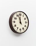 Brown clock on white office wall near noon. Brown simple plastic wall clock on the wall of office and concept of running out of time Royalty Free Stock Photo