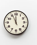 Brown clock on white office wall near noon Stock Photo