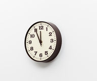 Brown clock on white office wall near noon. Brown simple plastic wall clock on the wall of office and concept of running out of time Stock Images