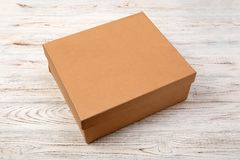 Brown closed cardboard box on a wooden background. top view, blank for you design.  royalty free stock images