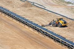 Brown coal open pit landscape with conveyor belt and dozer. In Garzweiler mine Germany royalty free stock photo