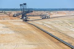 Brown coal open pit landscape with digging excavator in Germany. Brown coal open pit landscape with enormous digging excavator in Garzweiler mine Germany stock photos