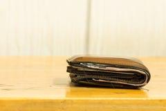Brown cobre a carteira dos homens com as cédulas na textura de madeira marrom Imagens de Stock