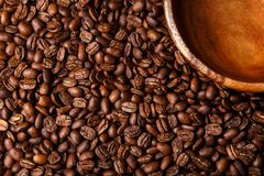 Brown coffee beans background with wooden dish Royalty Free Stock Photos