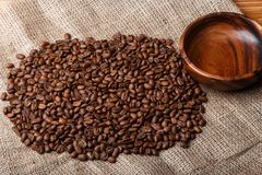 Brown coffee beans on the bag with empty wooden dish Stock Photography