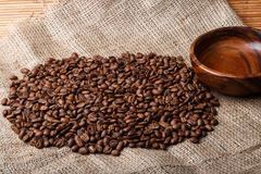 Brown coffee beans on the bag with empty wooden dish Royalty Free Stock Photo