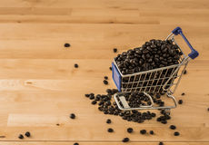 Brown coffee beans in cart on wood background Stock Image