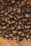 Brown coffee beans, closeup of macro coffee beans for background and texture. On brown wooden board. Royalty Free Stock Image