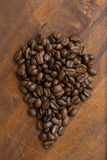 Brown coffee beans in shape of drop, closeup of macro coffee beans for background and texture. On brown wooden board. Royalty Free Stock Images
