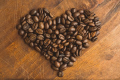 Brown coffee beans in  shape of heart, closeup of macro coffee beans for background and texture. On brown wooden board. Brown coffee beans in  shape of heart Stock Image