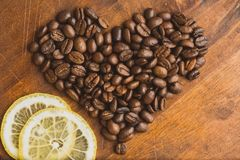 Brown coffee beans in shape of heart with lemon, closeup of macro coffee beans for background and texture. On brown wooden board Stock Images
