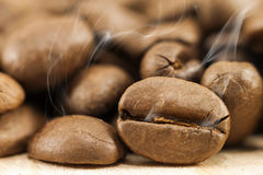 Brown coffee beans with white smoke vapour on yellow textured wo. Oden board background close up Royalty Free Stock Photo