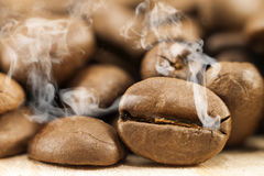 Brown coffee beans with white smoke vapour on yellow textured wo. Oden board background close up Royalty Free Stock Image