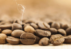 Brown coffee beans with white smoke vapour on yellow textured wo. Oden board background close up Stock Photography