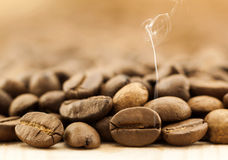 Brown coffee beans with white smoke vapour on yellow textured wo. Oden board background close up Stock Photos