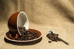 Brown Coffee cup with beans flowing Royalty Free Stock Photos