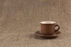 Brown coffee cup  on burlap. Empty Brown coffee cup  on burlap Royalty Free Stock Photos