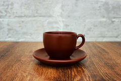 Brown coffee cup with a saucer and aromatic smoke on the wooden table close-up.  Royalty Free Stock Images