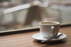 Brown coffee cup on a table. With a teespoon Royalty Free Stock Photos