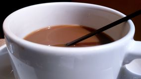 Brown coffee in a white cup with black straw. Close up image of brown coffee in a white cup with black straw Stock Photo