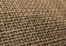 Brown color hessian cloth sack texture with blur effect. Stock Image