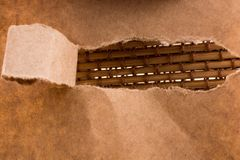 Brown color torn notepaper. On a straw texture background Royalty Free Stock Image