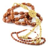 Brown colored very big rosary beads with small one isolated on white. Brown colored big bakelite rosary beads with gold plated silver tassel and small one stock image