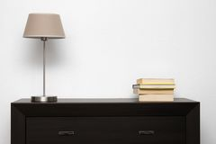 Brown commode with lamp and books in minimalism interior Stock Images