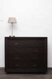 Brown commode with lamp in minimalism interior Royalty Free Stock Images