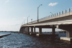 Brown Concrete Bridge Above Body of Water Under Blue Sky and White Clouds Stock Image