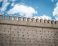 Brown Concrete Castle Wall Under Cumulos Clouds stock image