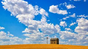 Brown Concrete House Near Tower Under Cloudy Sky Stock Photo