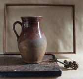 Brown contry still life. Brown country still life with pitcher, frame, stone and cone Stock Photography