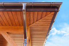Brown copper gutter under a cloudy blue sky. Stock Image