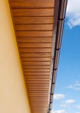 Brown copper gutter under a cloudy blue sky. Royalty Free Stock Image