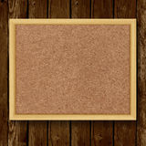 Brown cork board in a frame on wood background. 