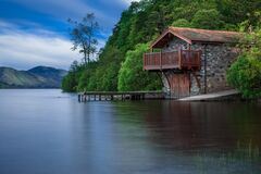 Brown Cottage Near Blue Body of Water during Daytime Royalty Free Stock Photography