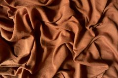 Brown cotton fabric in soft folds. Brown cotton jersey fabric in soft folds Stock Image