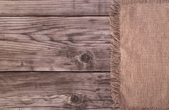 Brown cotton napkin on table. Brown cotton napkin from right side of old wooden background top view Royalty Free Stock Photo
