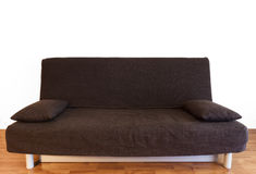 Brown couch in studio. Interior of studio, brown couch with pillows isolated on white Stock Image